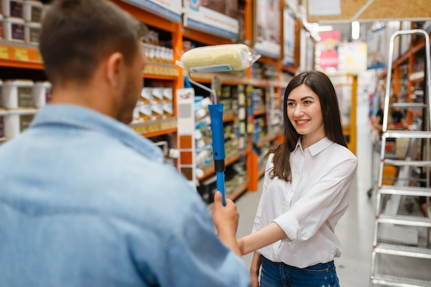 Young couple buying repair tools in hardware store