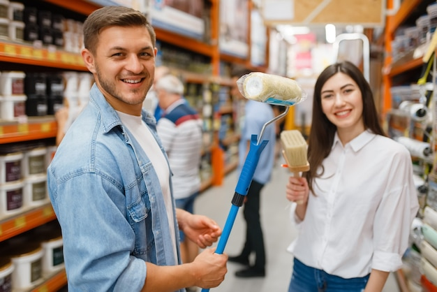 Young couple buying repair tools in hardware store.