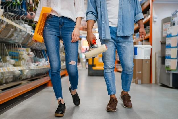 Молодая пара покупает валик для рисования, кисть и поднос в хозяйственном магазине