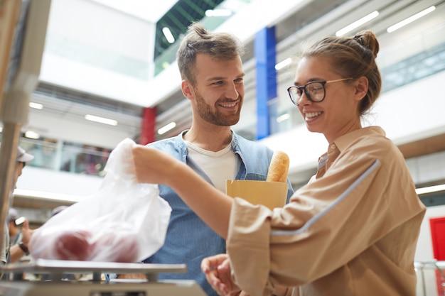 Молодая пара покупает овощи в супермаркете