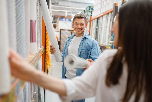 Молодая пара покупает обои в хозяйственном магазине. покупатели мужского и женского пола рассматривают товары в магазине своими руками