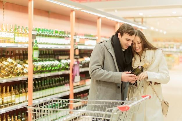 Молодая пара покупает вино