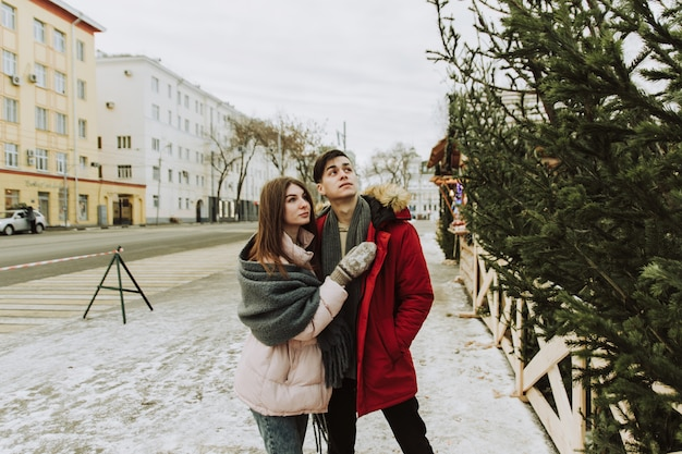 A young couple buys a christmas tree at the market in their home. concept a symbol of the christmas