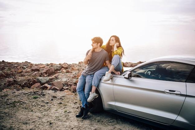 ビーチに駐車したスポーツカーで若いカップル。車の旅でのロマンスと愛。
