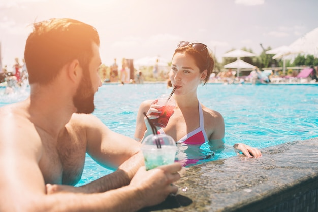 Young couple by the swimming pool. man and women drinking cocktails in the water.