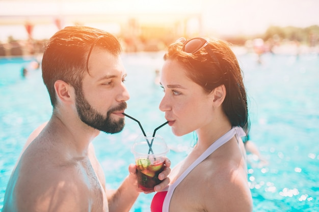 Young couple by the swimming pool. man and women drinking cocktails in the water