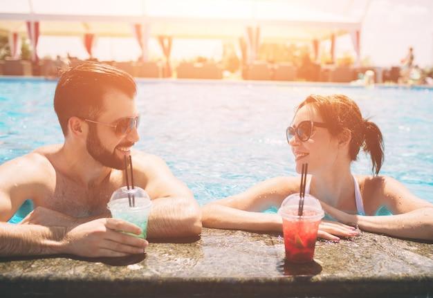 スイミングプールのそばの若いカップル