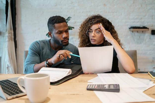 自宅からラップトップで請求書を計算して支払う若いカップル。毎月の予算を計画しているカップル。