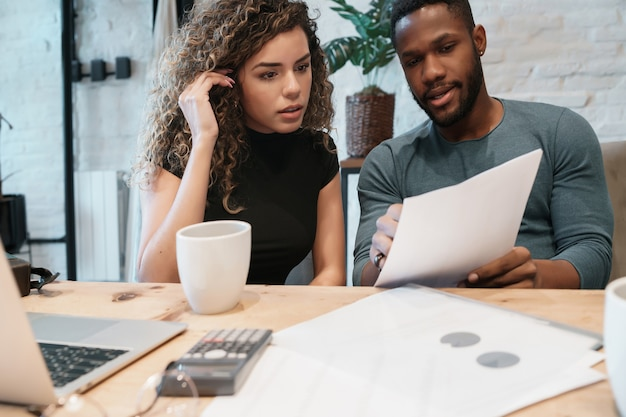 Young couple calculating and paying bills on a laptop from home. couple planning monthly budget.