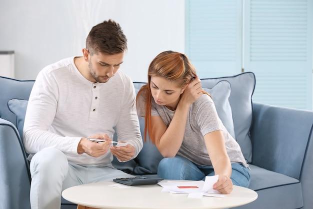 집에서 세금을 계산하는 젊은 부부