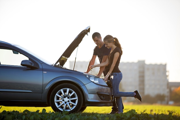 Young couple at car with popped hood checking oil level in engine