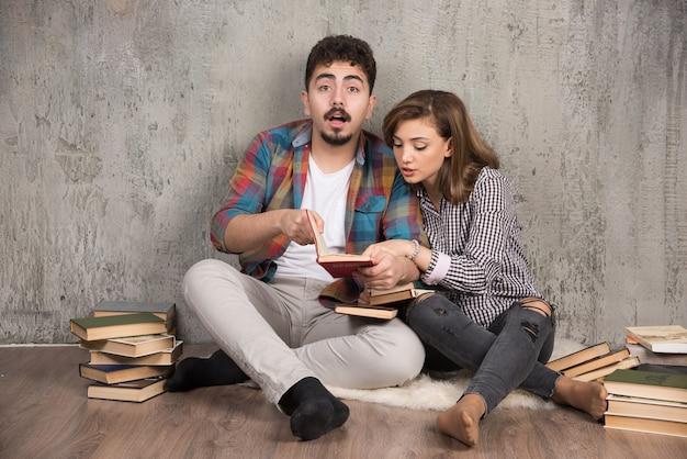 床に座って面白い本を注意深く読んでいる若いカップル