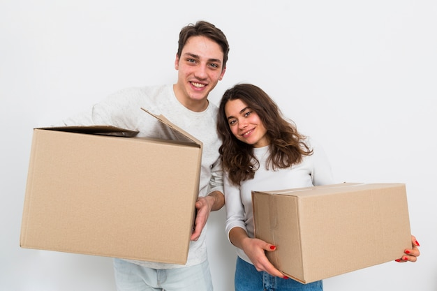 Young couple carrying cardboard boxes in hand isolated on white background