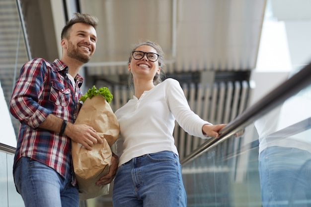 Young couple carrying grocery bag