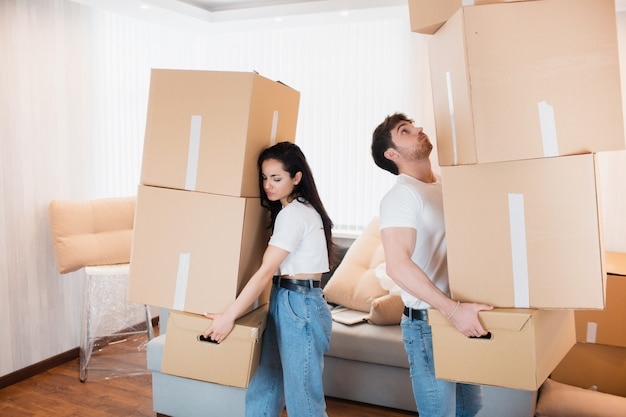 Young couple carrying many cardboard boxes one by one at new home. moving house.