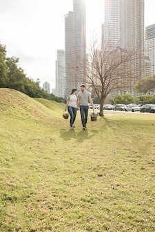 Young couple carrying wicker basket walking together in the park