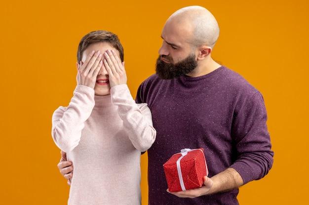 Giovane coppia in abiti casual uomo barbuto che dà un regalo alla sua ragazza sorpresa e felice che si copre gli occhi con le mani per celebrare san valentino in piedi sul muro arancione