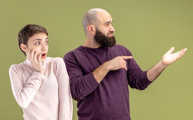 Coppia giovane in abiti casual barbuto uomo e donna con i capelli corti alla ricerca da parte di essere confuso e sorpreso per celebrare il giorno di san valentino in piedi su sfondo verde