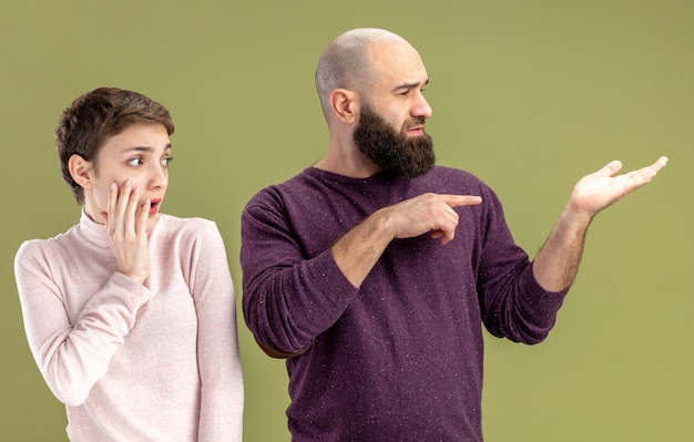 Young couple in casual clothes bearded man and woman with short hair looking aside being confused and surprised valentines day concept standing over green wall