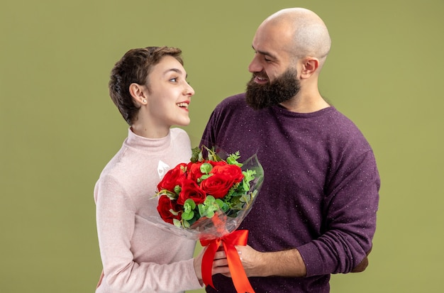 Young couple in casual clothes happy bearded man giving a bouquet of red roses to his smiling girlfriend celebrating valentines day standing over green wall