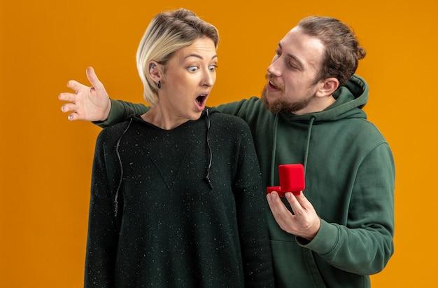 Giovane coppia in abiti casual uomo felice che fa proposta con anello di fidanzamento nel riquadro rosso alla sua fidanzata stupita e sorpresa il giorno di san valentino concetto in piedi sopra il muro arancione