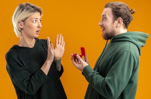 Coppia giovane in abiti casual uomo felice che fa proposta con anello di fidanzamento nel riquadro rosso al suo concetto di ragazza confusa e scontenta in piedi sopra il muro arancione