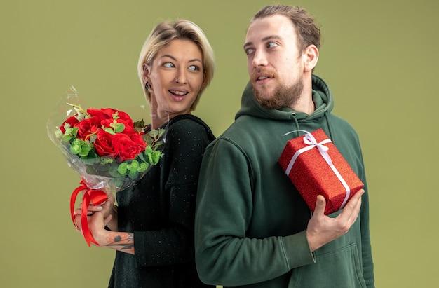 Giovane coppia in abiti casual uomo felice con presente e donna con fiori per celebrare il giorno di san valentino in piedi schiena contro schiena su sfondo verde