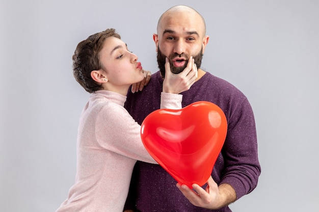 Giovane coppia in abiti casual donna felice che tocca le guance del suo timido sorridente ragazzo barbuto che tiene palloncino a forma di cuore che celebra il giorno di san valentino in piedi sul muro bianco