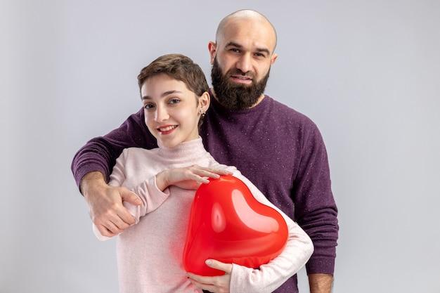 Giovane coppia in abiti casual uomo e donna che tiene il palloncino a forma di cuore sorridendo allegramente felice nell'amore che celebra il giorno di san valentino in piedi sul muro bianco