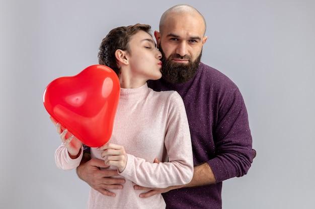 Giovane coppia in abiti casual uomo e donna azienda palloncino a forma di cuore donna che bacia il suo ragazzo felice che celebra il giorno di san valentino in piedi sopra il muro bianco