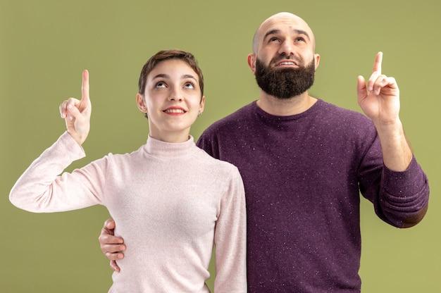 Coppia giovane in abiti casual donna con i capelli corti e uomo barbuto guardando in alto che mostra le dita indice felice e positivo per celebrare il giorno di san valentino in piedi su sfondo verde