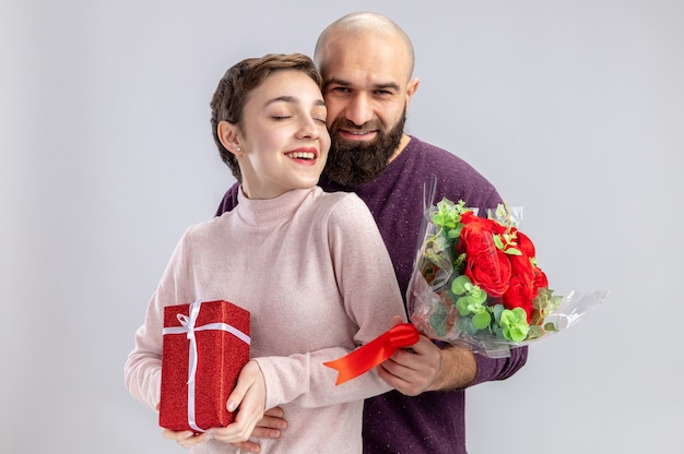 Young couple in casual clothes woman with short hair with present and bearded man with bouquet of red roses embracing happy in love celebrating valentines day standing over white background