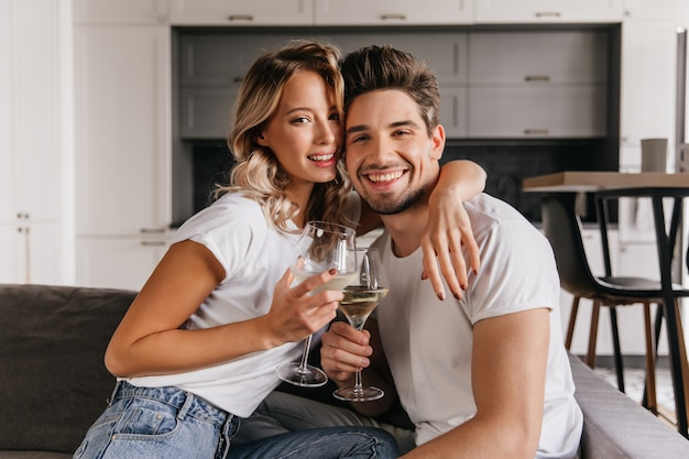 自宅で記念日を祝う若いカップル。夫とシャンパンを飲んで満足している女性。
