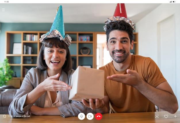 집에 머무는 동안 화상 통화에 온라인으로 생일을 축하하는 젊은 부부. 새로운 정상적인 라이프 스타일 개념.
