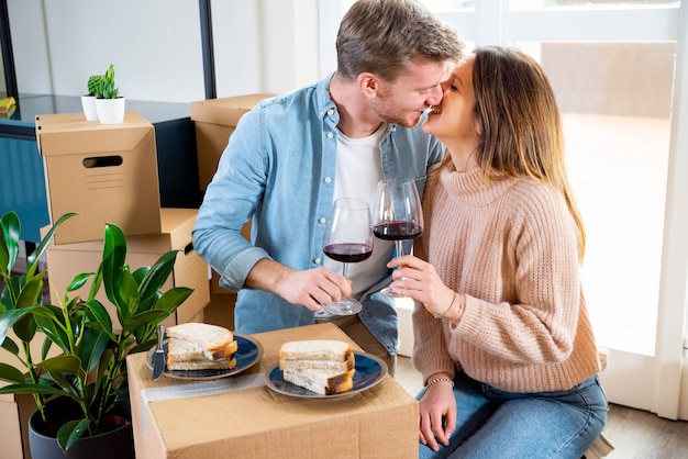 Young couple celebrating buying new house while drinking wine on cardboard