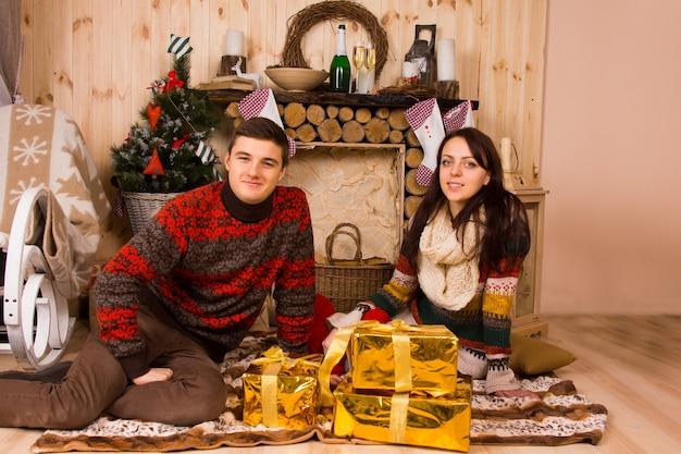 カメラに微笑んでスタイリッシュな金で包まれた贈り物と炉床の前の敷物の床に座っている素朴なキャビンでクリスマスを祝う若いカップル