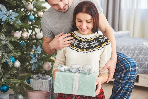 Young couple celebrating christmas. a man suddenly presented a present to his wife. the concept of family happiness and well-being