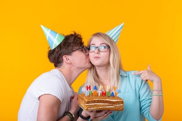 종이 모자를 쓴 젊은 부부의 매력적인 남자와 귀여운 소녀는 어리석은 얼굴을 하고 노란색 배경에 생일이 새겨진 케이크를 손에 들고 있습니다. 개념 인사말 및 장난