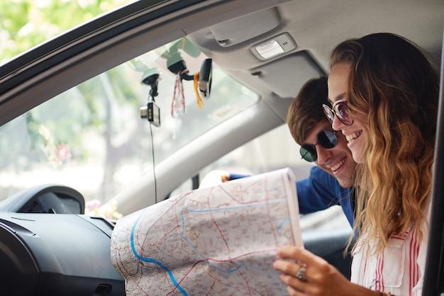 Молодая пара проверяет карту во время путешествия
