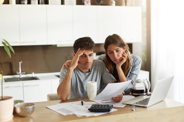 그들의 가족 예산을 확인하는 젊은 부부