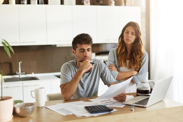 若いカップルが家族の予算をチェック