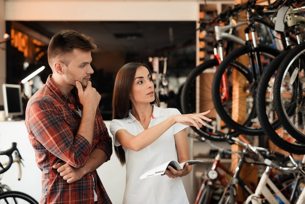 Young couple choose bike look at catalog in shop