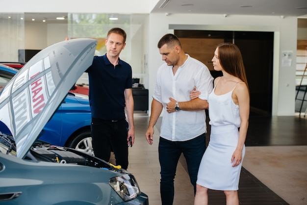 A young couple chooses a new car at the dealership and consults with a representative of the dealership. used cars for sale. dream fulfillment.