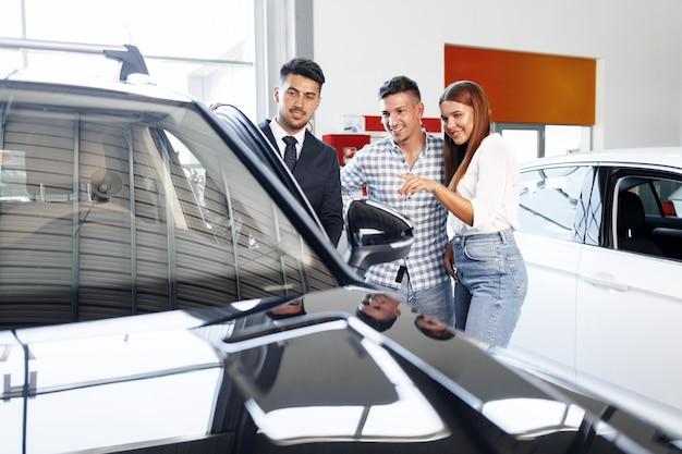 Молодая пара, выбирая автомобиль в автосалоне с менеджером, помогающим им