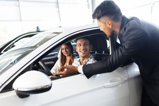 Молодая пара, выбирая автомобиль в автосалоне с помощью менеджера