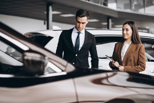 Молодая пара выбирает автомобиль в автосалоне