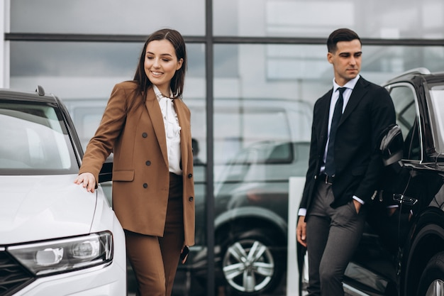 車のショールームで車を選ぶ若いカップル