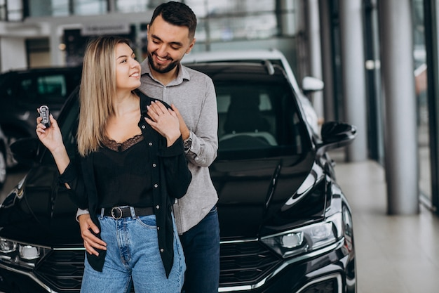 Young couple choosing a car in a car show room