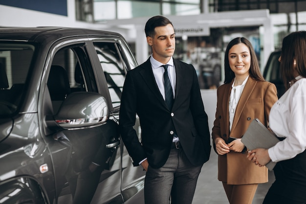 Young couple choosing a car in a car showroom