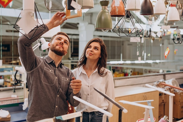 Young couple choosing chandelier in building center